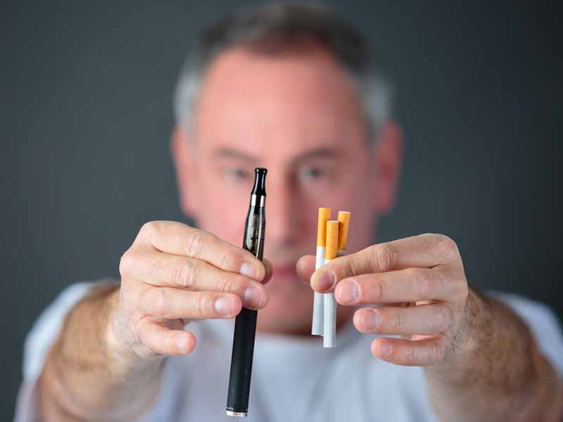 Man holding combustible cigarettes and e-cigarette