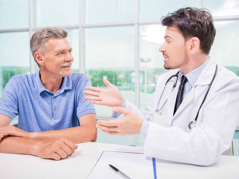 physician speaking with older male patient
