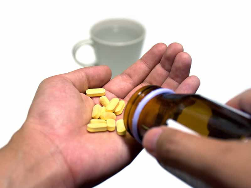 patient shaking pills out of bottle into hand