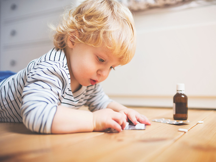 Young child playing with blister pack of pills