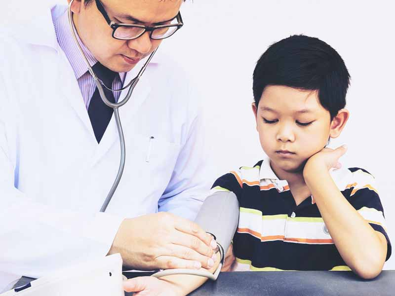 physician preparing to take young boy's blood pressure