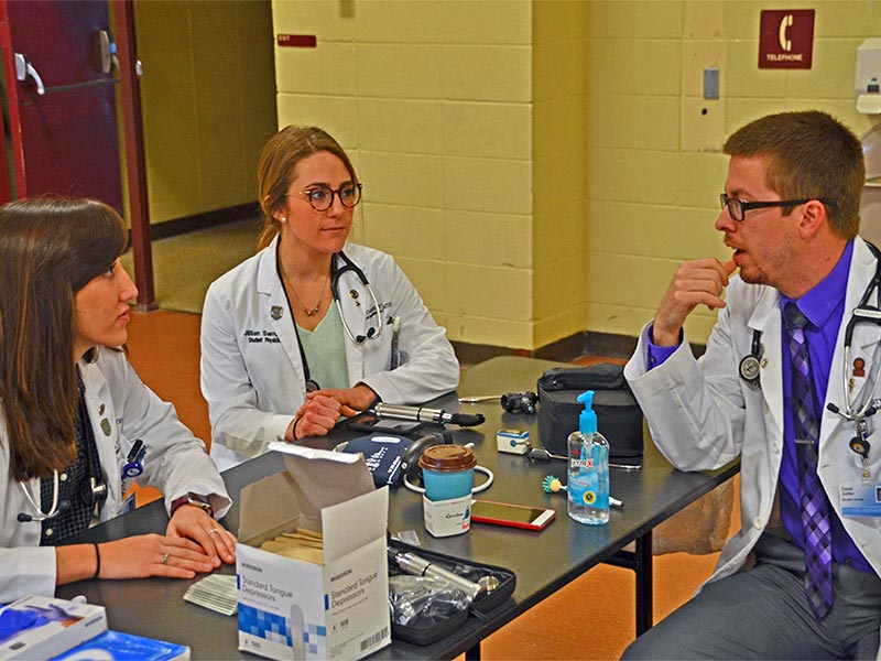 Three osteopathic medical students from A.T. Still University's Kirksville College of Osteopathic Medicine prepare to treat patients as part of a free health fair put on by Still Caring Health Connection-Volunteers in Medicine.