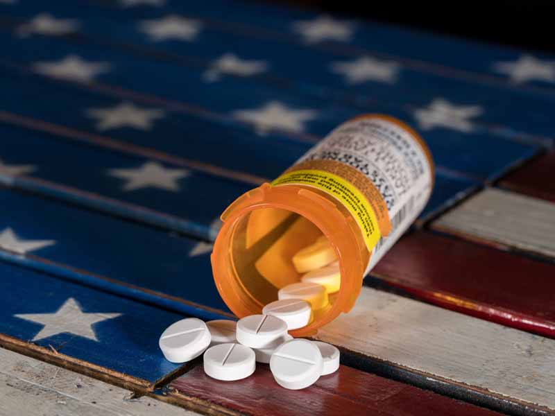 tablets spilling out of pill bottle atop US flag-decorated wooden surface