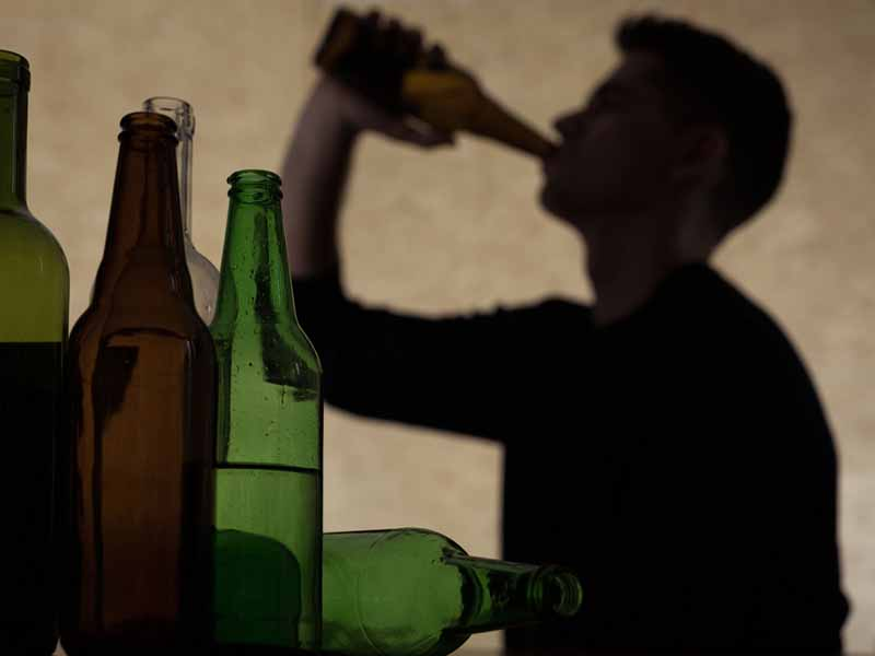 silhouette of young man drinking from bottle
