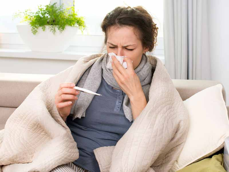 women with flu symptoms bundled up on couch