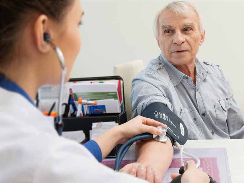clinician taking older man's blood pressure