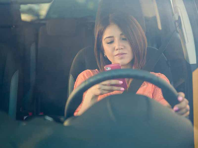 teen girl looking at phone while driving