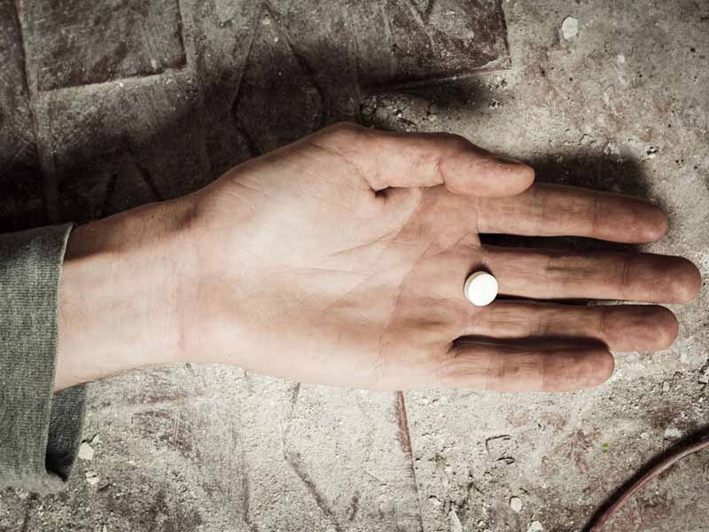 outflung hand with pill in palm
