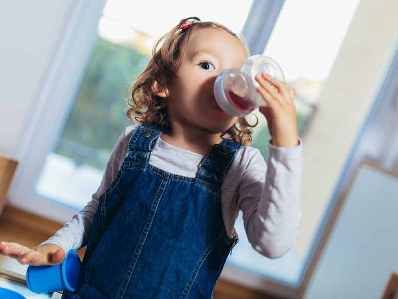 Adorable child drinking juice from bottle.