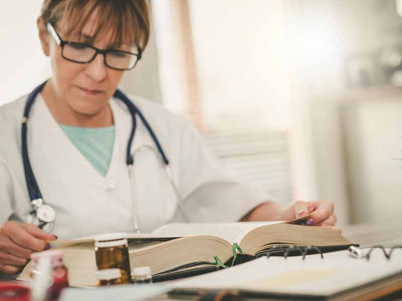 Female doctor reading a textbook in medical office
