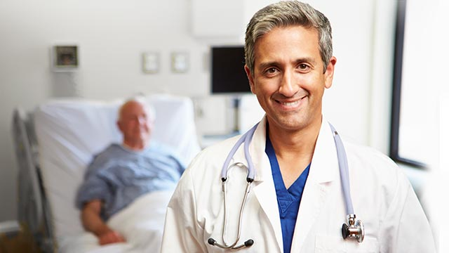 [Portrait Of Male Doctor With Patient In Background]
