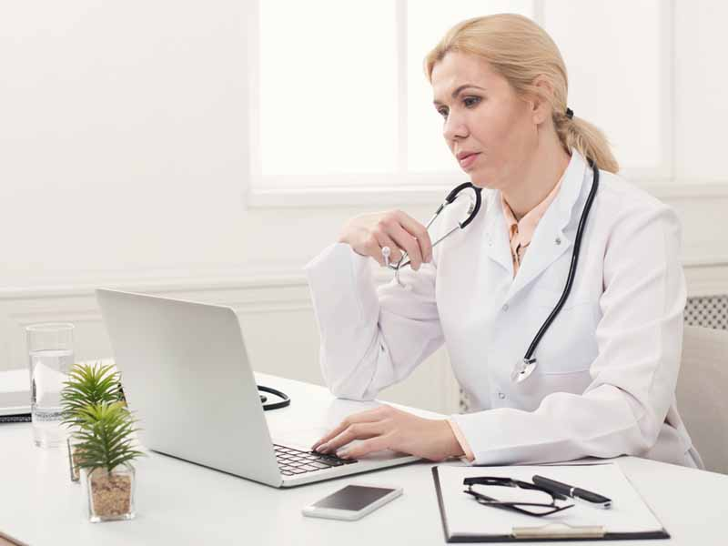 female physician using laptop