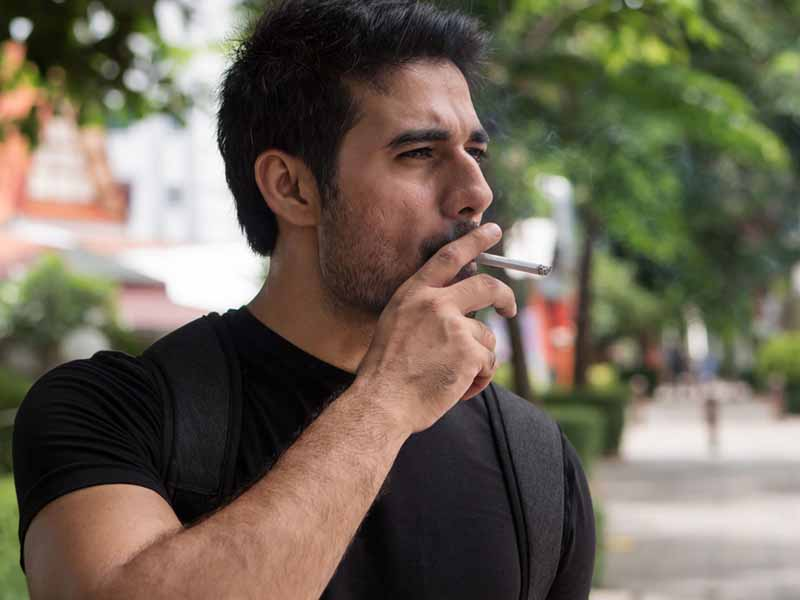 adult male smoking cigarette