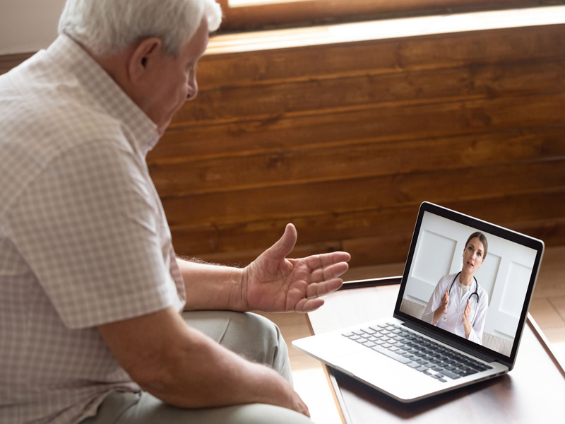 elderly patient speaking with younger physician via telemedicine