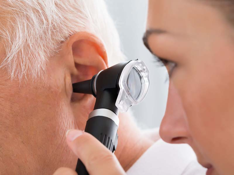 physician examining older patient's ear