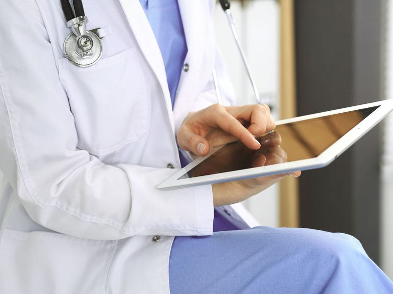 woman physician using tablet computer
